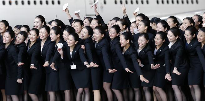 Nowo zatrudnione stewardessy linii lotniczych Japan Airlines pozują do zdjęcia na tle samolotu w barwach linii na lotnisku Haneda w Tokio. Stopa bezrobocia w Japonii spadła w październiku 2013 roku do 4 proc. Na początku roku wynosiła 4,2 proc. Fot. Kiyoshi Ota, Bloomberg's Best Photos 2013.