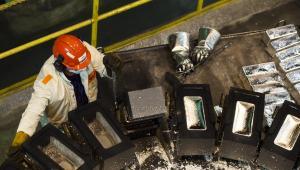 Huta Miedzi Głogów: pracownik huty wyjmuje wystudzone sztabki srebra z form