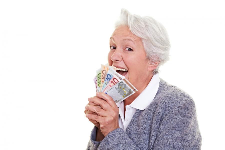 Seniorak z plikiem banknotów w dłoni